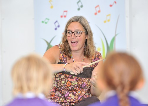 teacher leading musical activity in front of children